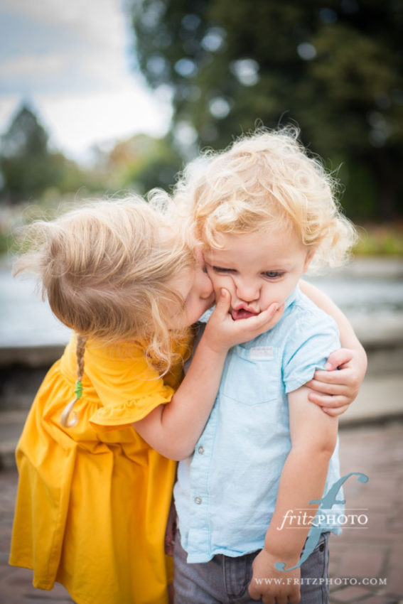 brother and sister being sweet during family portraits at peninsula park in portland oregon