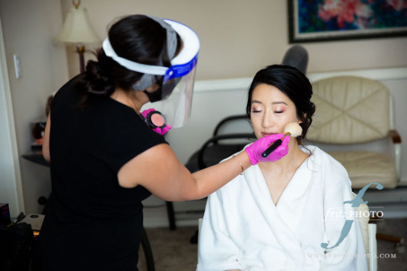 hair and makeup artist with face shield and gloves