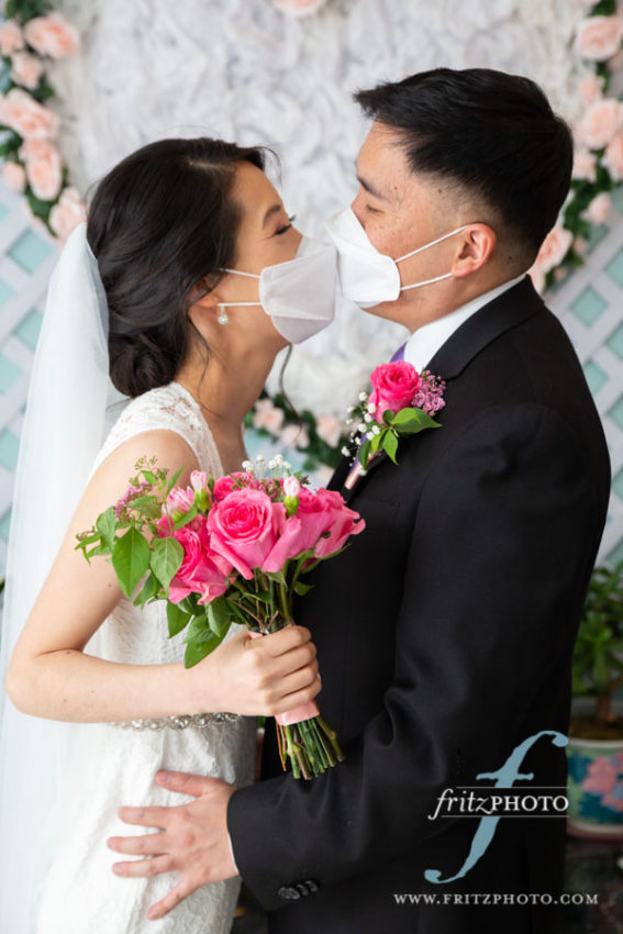 Bride and groom kissing with masks on