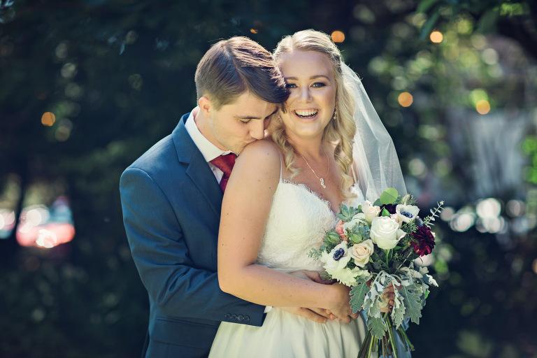 Groom kissing bride at Mcmenamins Cornelius Pass Roadhouse wedding